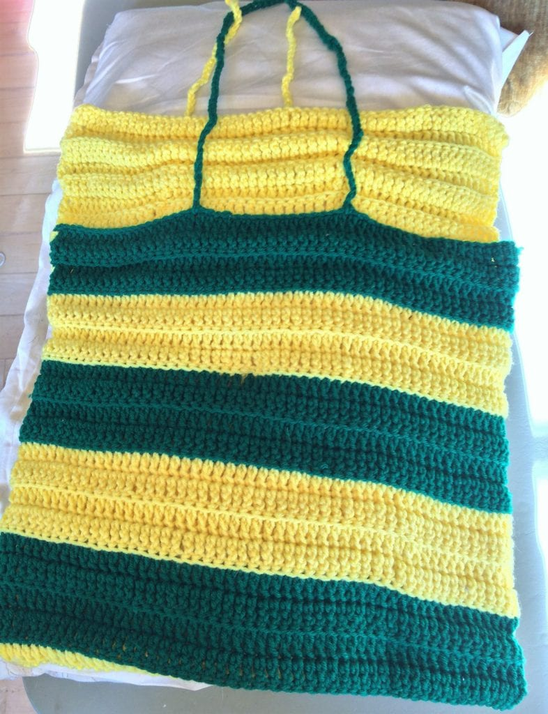 Green and gold crochet pillow covering laying flat