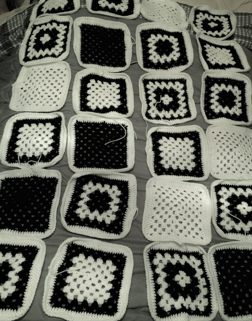 granny squares laying on bed for layout out the blanket pattern