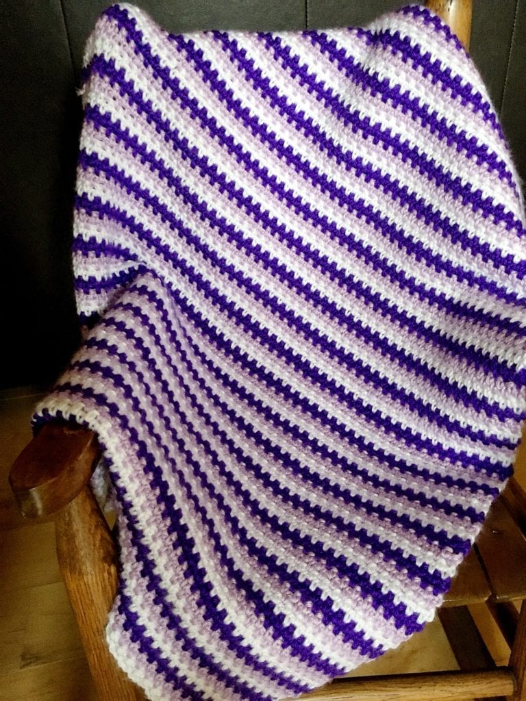 How to crochet a moss stitch baby blanket draped over a chair