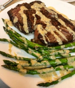 Rib Eye Steak Served with Asparagus and Creamy Garlic Butter Sauce