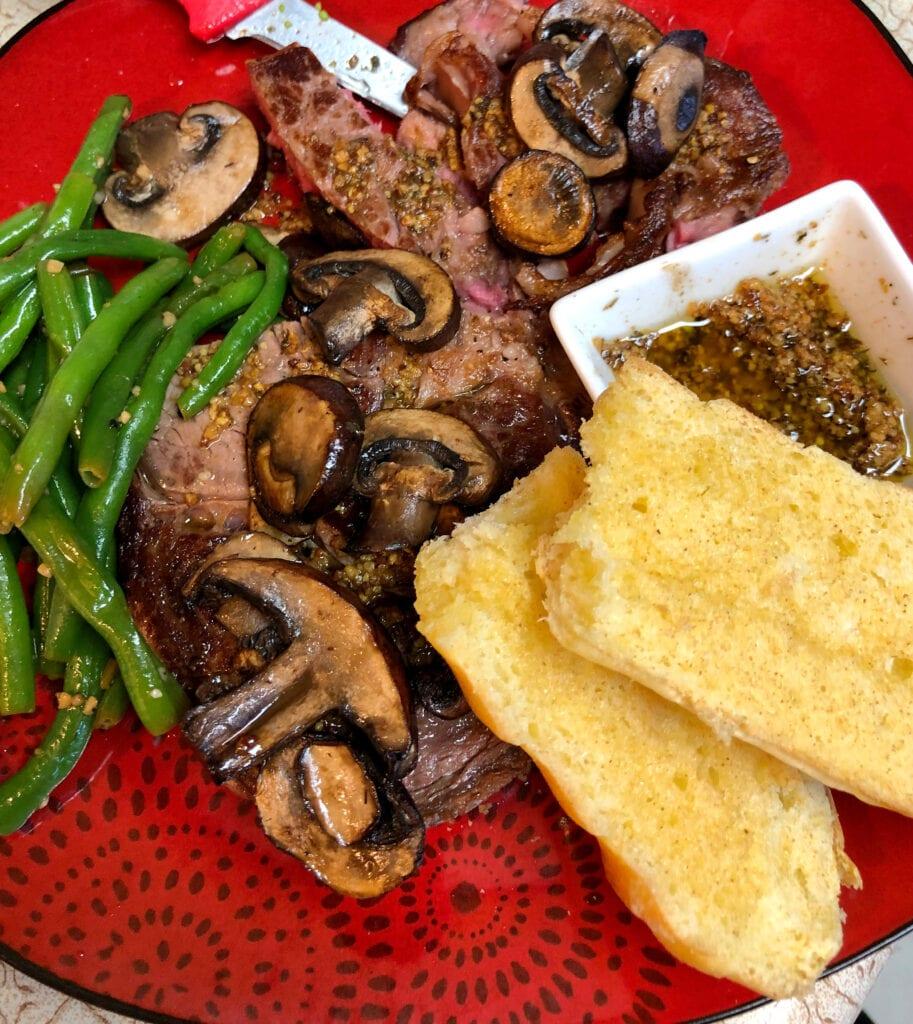 Green Beans, Steak, Fried Mushrooms, Mustard Butter Sauce, and Garlic Bread