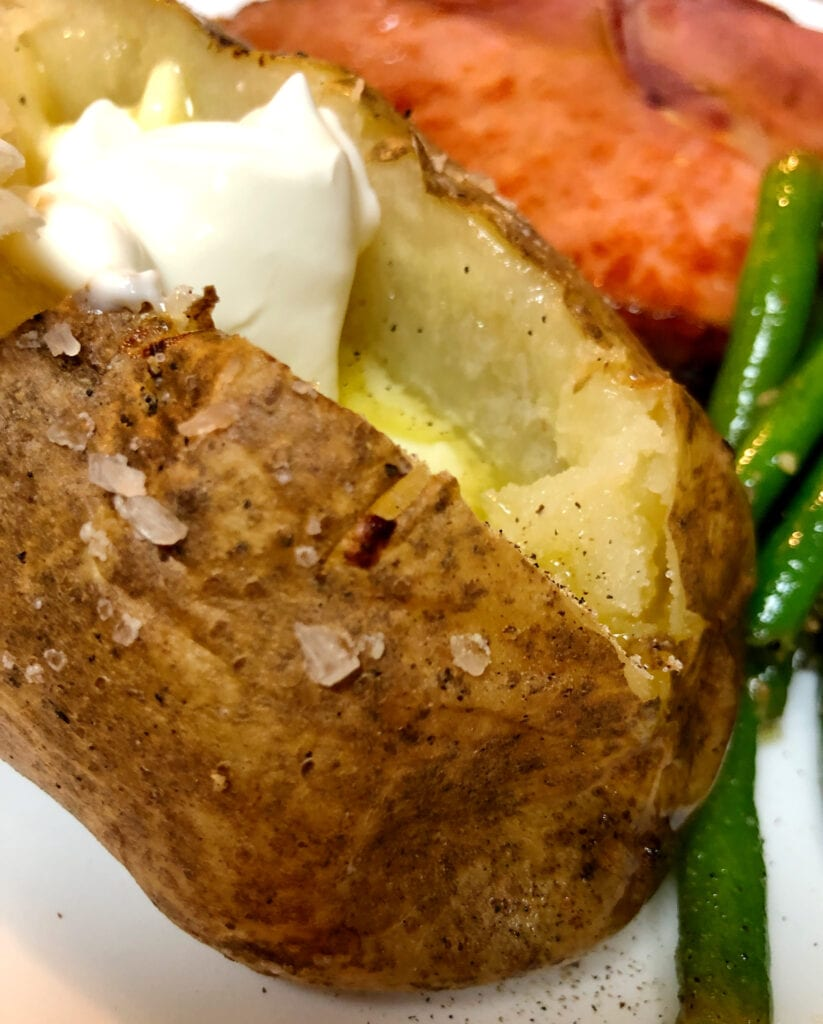 Perfectly Cooked Baked Potato with Sour Cream and Melted Butter