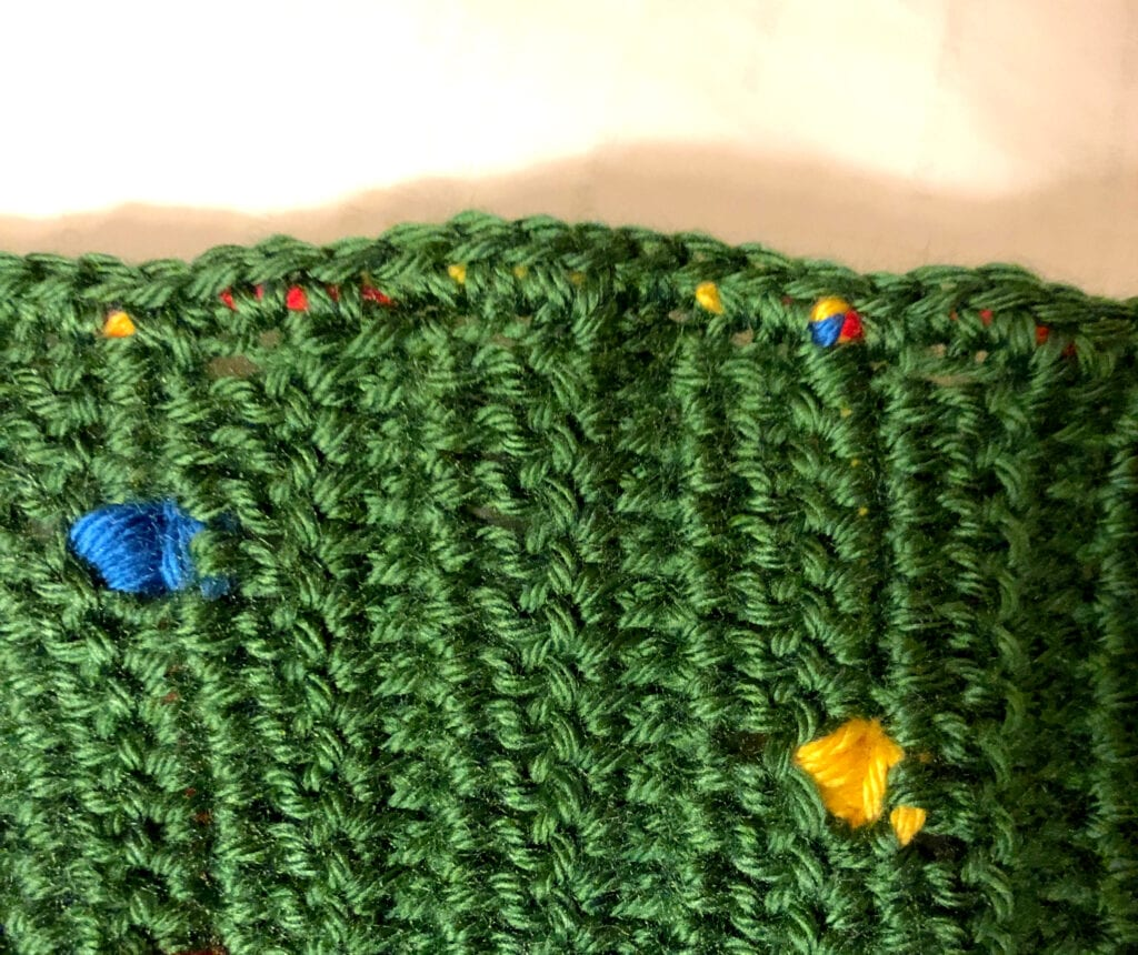 Completing Round 1 of Single Crochet Over Colored Yarn on Side of Blanket