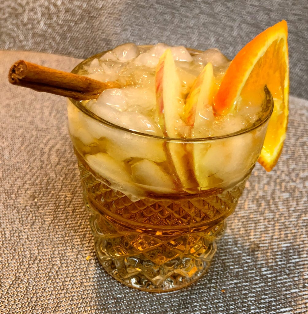 Garnishing a Fall Beverage with Orange and Apple Slices and Cinnamon Stick