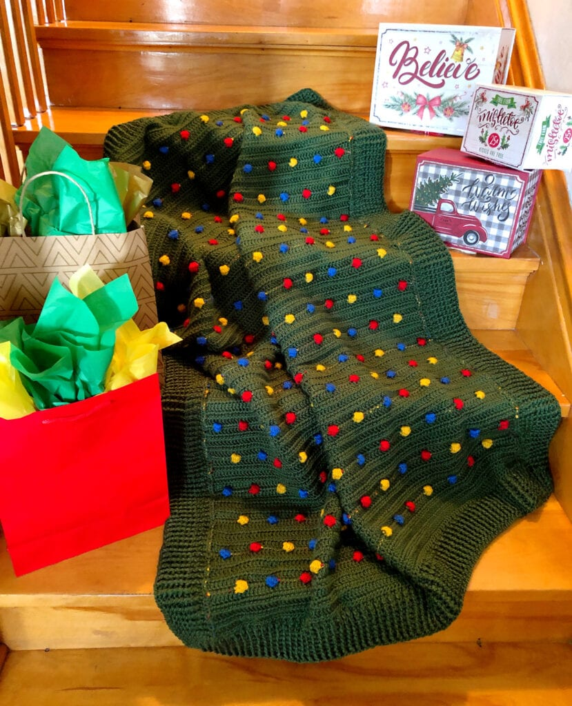 Festive Light Crochet Blanket on Steps with Holiday Boxes and Bags