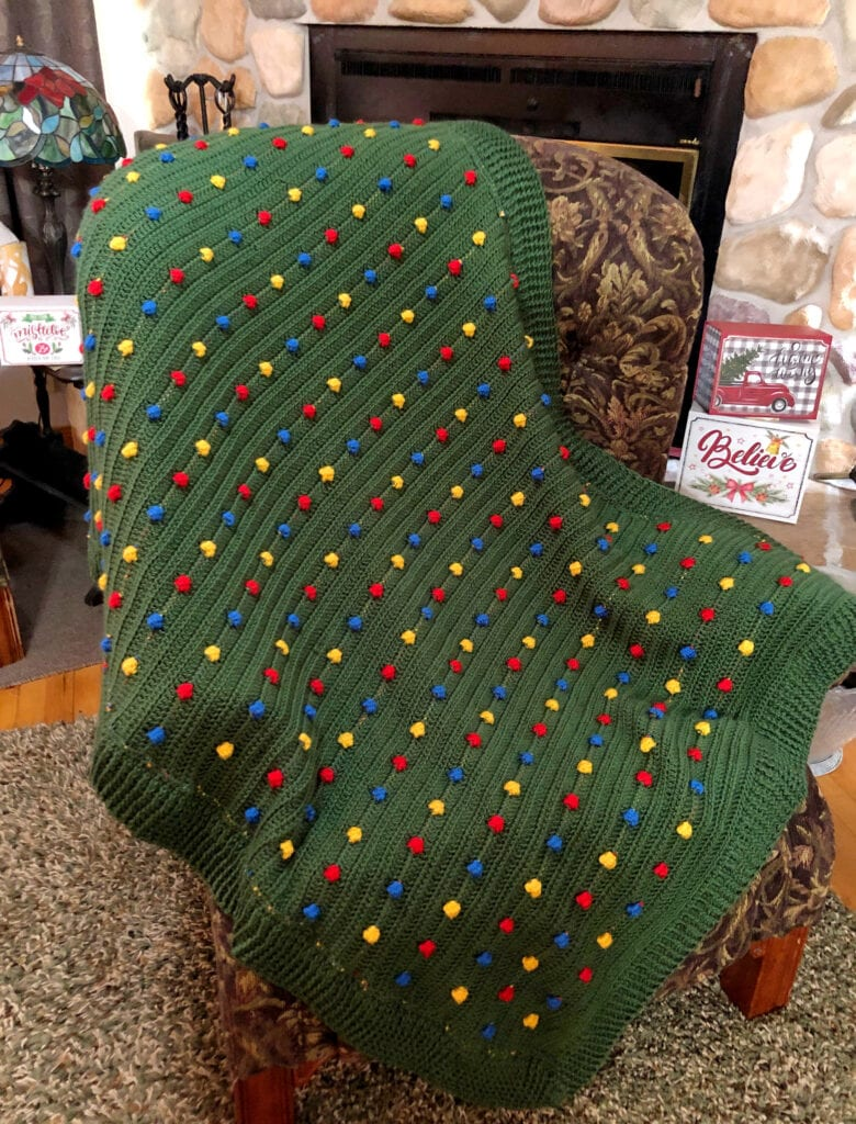 Crochet Christmas Blanket on a Chair in Front of Fireplace