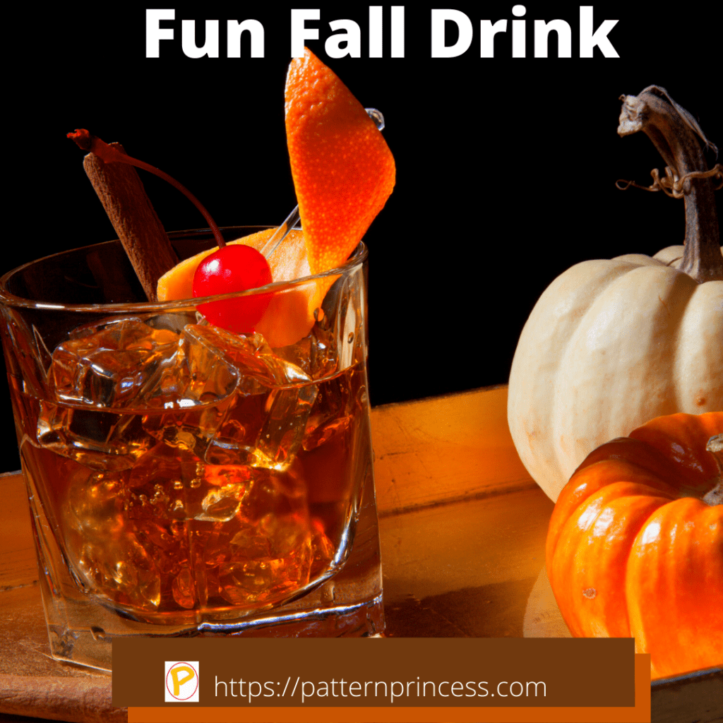 Fun Fall Bourbon Drink Garnished with Orange Rind Cherry and Cinnamon Stick