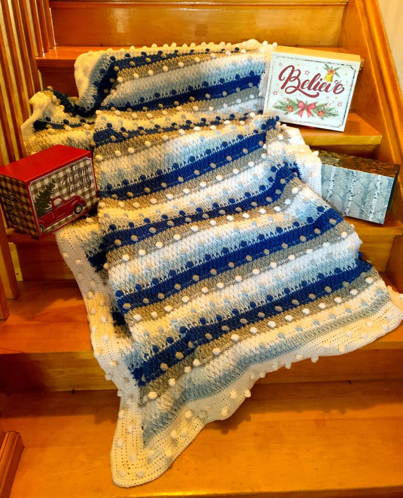 Shades of Blue Crochet Holiday Blanket Displayed with Christmas Decorations