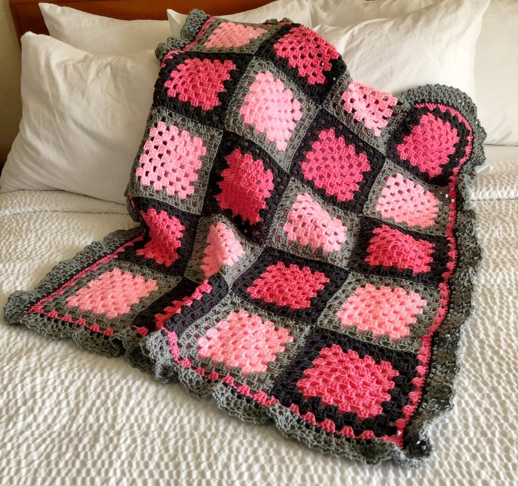 Pink and Grey Granny Square Blanket Shown on Bed